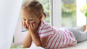Feche acima do retrato do livro de leitura bonito pequeno da menina na soleira em casa vídeos de arquivo
