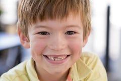 Feche acima do retrato do headshot de 7 ou 8 anos pequenos novos do menino idoso com o sorriso engraçado doce dos dentes feliz e  Imagens de Stock