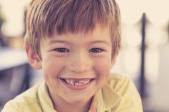 Feche acima do retrato do headshot de 7 ou 8 anos pequenos novos do menino idoso com o sorriso engraçado doce dos dentes feliz e  Imagem de Stock Royalty Free