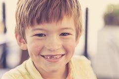 Feche acima do retrato do headshot de 7 ou 8 anos pequenos novos do menino idoso com o sorriso engraçado doce dos dentes feliz e  Fotografia de Stock