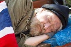 Feche acima do retrato do homem desabrigado que dorme no banco no parque da cidade Imagens de Stock