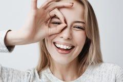 Feche acima do retrato do sorriso fêmea caucasiano louro alegre bonito, demonstrando os dentes brancos, olhando a câmera fotos de stock royalty free