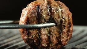 Feche acima do rissol suculento grande que est? sendo grelhado, tenazes de brasa do hamburguer do ferro que viram o rissol ao out filme