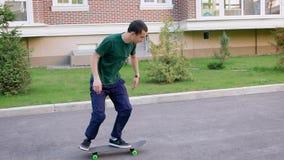 Feche acima do skater novo vestido na camisa verde ocasional, na calças azul e nas sapatilhas montando na superfície plana dentro vídeos de arquivo