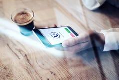Feche acima do smartphone genérico do projeto com os ícones da chamada entrante que realizam na mão fêmea Café do copo na tabela  Foto de Stock Royalty Free