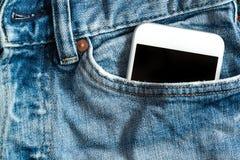 Feche acima do smartphone no bolso dianteiro em calças Imagens de Stock