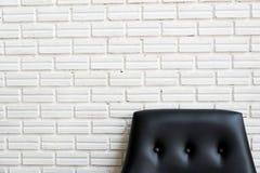 Feche acima do sofá preto clássico e da parede de tijolo branca Imagens de Stock Royalty Free