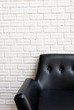 Feche acima do sofá preto clássico e da parede de tijolo branca Fotos de Stock Royalty Free