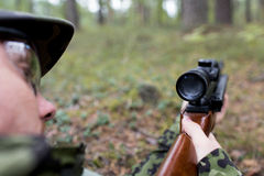Feche acima do soldado ou do caçador com a arma na floresta fotografia de stock