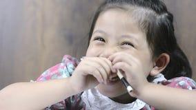 Feche acima do sorriso alegre e do lápis da menina asiática pequena bonito à disposição filme