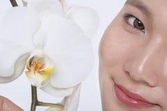 Feche acima do sorriso da jovem mulher e de uma flor branca bonita, meia exibição da cara, tiro do estúdio Fotografia de Stock