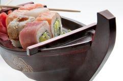 Feche acima do sushi do sashimi ajustado com hashis e soja em uma bandeja servindo do barco fotos de stock royalty free
