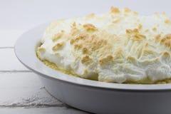 Feche acima do tarte de limão e merengue sem cortes inteiro na madeira rústica branca Imagem de Stock Royalty Free