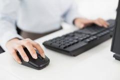 Feche acima do teclado e do rato de computador das mãos Fotografia de Stock