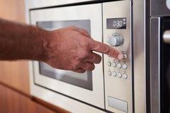 Feche acima do temporizador do ajuste da mão no forno micro-ondas imagem de stock