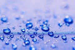 Feche acima do teste padrão das gotas da água sobre um pano impermeável azul imagem de stock royalty free