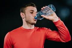 Feche acima do tiro da água potável europeia nova atrativa do desportista da garrafa, sportswear vermelho vestindo, relaxando apó Fotografia de Stock Royalty Free