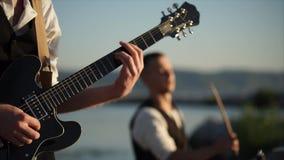 Feche acima do tiro da guitarra do ritmo, jogos de um homem com a ajuda de um mediador vídeos de arquivo