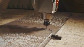 Feche acima do tiro da máquina do cnc, que é contratada em cortar uma parte de vidro filme