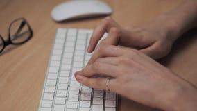 Feche acima do tiro da mão da mulher que datilografa no teclado de computador no escritório moderno na tabela vídeos de arquivo