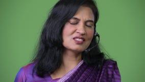 Feche acima do tiro da mulher indiana bonita feliz madura como o representante do centro de atendimento que fala em auriculares video estoque