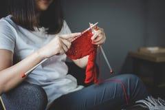 Feche acima do tiro das mãos da jovem mulher que fazem malha um handicra vermelho do lenço fotos de stock royalty free