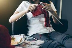 Feche acima do tiro das mãos da jovem mulher que fazem malha um handicra vermelho do lenço fotografia de stock royalty free