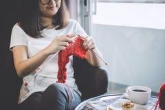 Feche acima do tiro das mãos da jovem mulher que fazem malha um handicra vermelho do lenço fotografia de stock