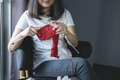 Feche acima do tiro das mãos da jovem mulher que fazem malha um handicra vermelho do lenço imagens de stock royalty free