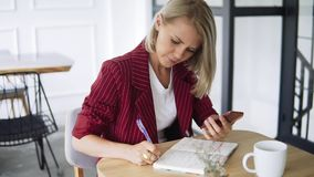Feche acima do tiro das mãos da mulher de negócio bem sucedida bonita e nova com bloco de notas em um café, trabalhando como um f vídeos de arquivo
