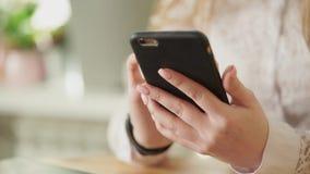 Feche acima do tiro das mãos de uma moça, que guardando um smartphone vídeos de arquivo