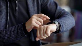 Feche acima do tiro das mãos do ` um s do homem de negócios, que faz a varredura de mensagens em um relógio esperto a fim verific filme