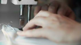 Feche acima do tiro das mãos fêmeas que trabalham na máquina de costura desenhista do conceito da jovem mulher que trabalha em um video estoque