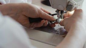 Feche acima do tiro das mãos fêmeas que trabalham na máquina de costura o alfaiate está reparando a máquina de costura filme