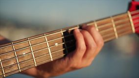 Feche acima do tiro das mãos do ` s dos homens, que classifica as cordas no fretboard da guitarra video estoque