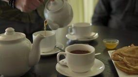 Feche acima do tiro das mãos do ` s do homem, ele derrama o chá da chaleira nos copos video estoque