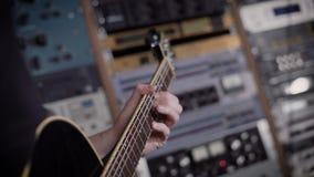 Feche acima do tiro das mãos do ` s do homem, que classifica as cordas e cria cordas a fim impor sons na música no seu video estoque