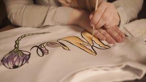 Feche acima do tiro das mãos do ` um s do adolescente, que decora sua roupa usando o desenho da aquarela filme