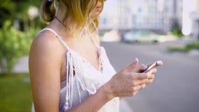Feche acima do tiro das mãos do ` um s da mulher, que guarda um smartphone, os olhares da senhora nas redes sociais de seus amigo video estoque