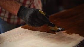 Feche acima do tiro das mãos do ` um s do homem, que cobre a superfície da tabela com a laca filme