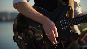 Feche acima do tiro das mãos do ` um s do homem, que joga a guitarra do ritmo com um mediador video estoque