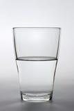 Feche acima do tiro de um vidro de água meio cheio Imagens de Stock Royalty Free