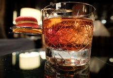 Feche acima do tiro do cocktail de Negroni com bolinho de amêndoa de campari imagem de stock