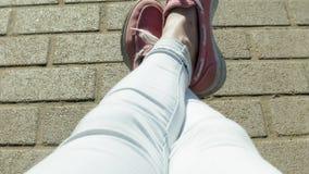 Feche acima do tiro dos pés do ` s da mulher nas sapatilhas brilhantes, que pisaram lentamente na areia molhada, provavelmente ao video estoque