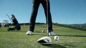 Feche acima do tiro em um campo de golfe quando um jogador de golfe bate a bola de golfe branca com um golfe