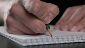 Feche acima do tiro macro super de uma escrita da mão do homem algo no lápis de papel do caderno vídeos de arquivo