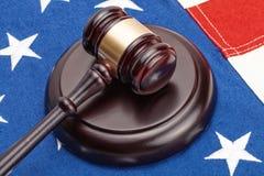 Feche acima do tiro do martelo de madeira do juiz sobre a bandeira do Estados Unidos fotografia de stock