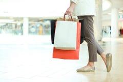 Feche acima do tiro do pé da jovem mulher que leva sacos de compras coloridos ao andar no shopping fotografia de stock royalty free