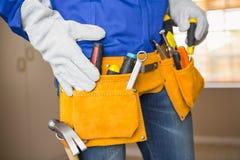 Feche acima do trabalhador manual na correia da ferramenta Fotografia de Stock