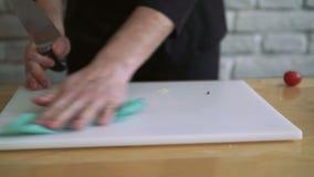 Feche acima do vídeo da faca de cozinha, placa na tabela Homem que leva embora o 4k vídeos de arquivo